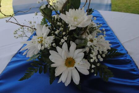 Table centerpiece of white daisies and chrysanthemums, blue tablecloth Foto de archivo