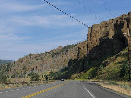 Cody, Wyoming, USA--July 2018: Winding road at North Fork Highway to Yellowstone National Park, with a vehicle on the road.