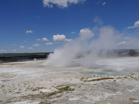 Scenic view of steam rising from the Clepsydra Geyser at the Lower Geyser Basin, Yellowstone National Park. Banco de Imagens