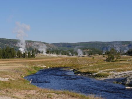 Wide shot of the Firehole River with hot water overflow and steam rising from multiple geysers at the Yellowstone National Park in Wyoming.