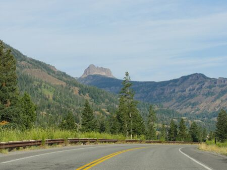 Winding sloping road at the North Fork Highway heading to the east entrance of Yellowstone National Park.