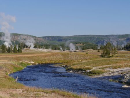 Hot water overflows into the Firehole River with steam rising from multiple geysers at the Yellowstone National Park in Wyoming.