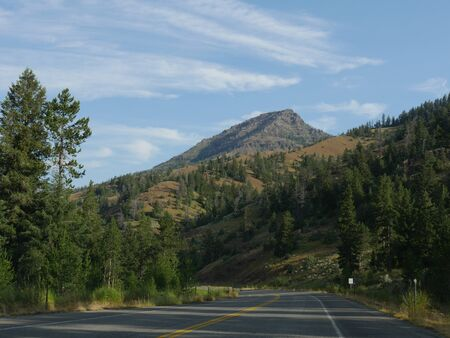 Winding sloping paved road at the North Fork Highway heading to the east entrance of Yellowstone National Park.