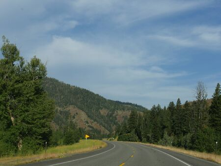 Winding road along North Fork Highway heading to the east entrance of Yellowstone National Park.
