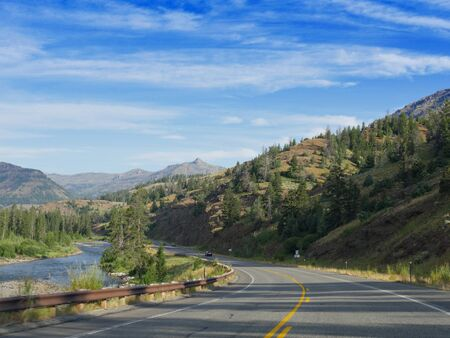 Cody, Wyoming, USA--July 2018: Winding road at the North Fork Highway with the north Fork Soshone River flowing along the road.