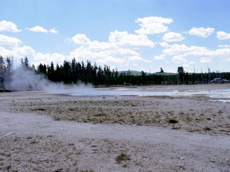 Lower Geyser Basin, wide view, with people walking on the boardwalks at Yellowstone National Park.