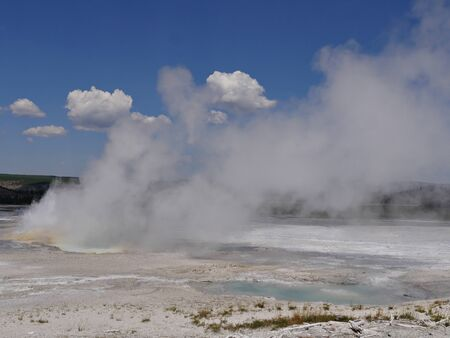 Medium wide shot of steam rising from the Clepsydra Geyser at the Lower Geyser Basin, Yellowstone National Park.