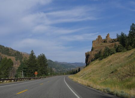 Beautiful view of a winding road with the Chimney Rock, an imposing rock formation along North Fork Highway to Yellowstone National Park.