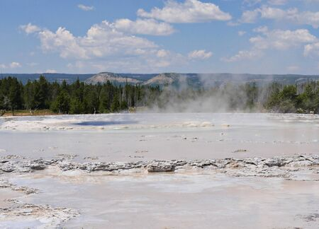 Wide shot of the fountain Paint Pot at Lower Geyser Basin, with clear skies at Yellowstone National Park, Wyoming.