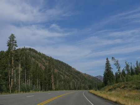 Scenic winding road along North Fork Highway heading to the east entrance of Yellowstone National Park. Stock Photo