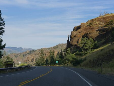 Winding road with the Chimney Rock, an imposing rock formation along North Fork Highway to Yellowstone National Park. Stock Photo