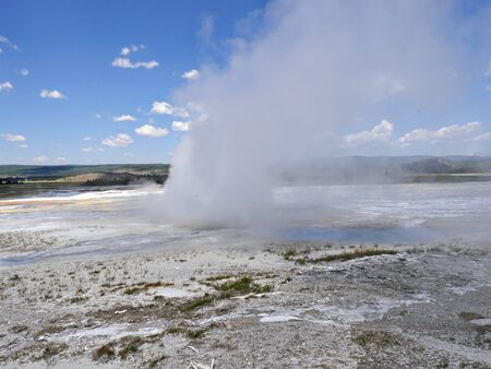 Wide shot of Clepsydra Geyser with steam shooting up at the Lower Geyser Basin, Yellowstone National Park.