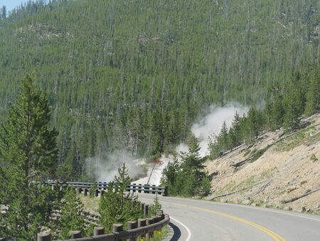 Scenic drives around the Yellowstone National Park in Wyoming, with steam rising from geysers by the road. Stock Photo