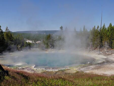 Close up view of the Emerald Spring with hot steam rising off at the Norris Geyser Basin at Yellowstone National Park, Wyoming.