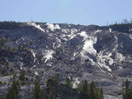 Upward view of the Roaring Mountain with steam spewing from numerous fumaroles at Yellowstone National Park, Wyoming.