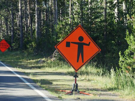 Roadside warning of flagman ahead at Yellowstone National Park.