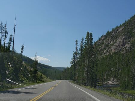 Scenic drives at Yellowstone National Park in Wyoming, with the Yellowstone River flowing along the road.