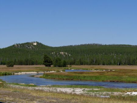 Scenic view of Yellowstone River flowing through the meadow at Yellowstone National Park, Wyoming.