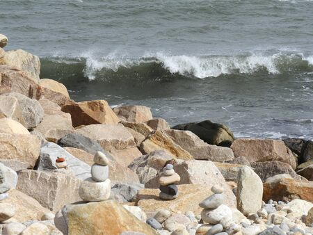 Waves roll toward big piles of rocks in on the shoreline Stock Photo