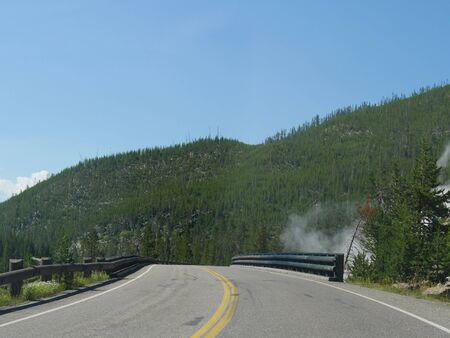 Beautiful views driving around the Yellowstone National Park in Wyoming, with steam rising from geysers by the road.