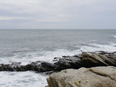 Limestone and rocky shoreline with foaming waves rolling in on a bleak day Stock Photo