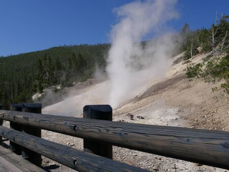 View of steam rising from geysers along the road at Yellowstone National Park with a log fence in the foreground.