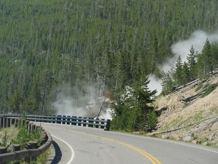 Scenic view of a winding road at Yellowstone National Park in Wyoming, with steam rising from geysers by the road.