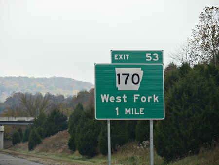 Roadside sign with exit directions to West Fork at Interstate 49 in Arkansas, USA.