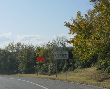 Wide shot with roadside welcome sign to Oklahoma at the border past Arkansas near Moffett.