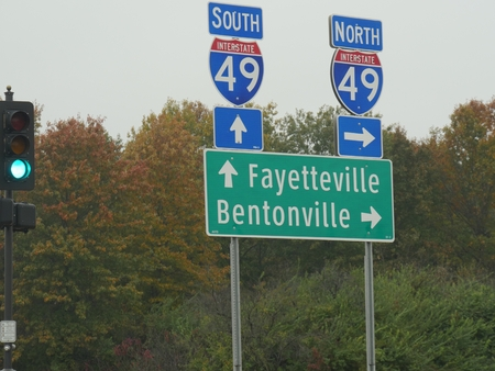 Roadside signs and directions to Fayetteville and Bentonville along Interstate 49 in Arkansas, USA.