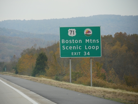 Roadside sign to Boston Mountains Scenic Loop in Arkansas, USA with colorful trees in autumn.