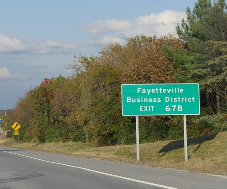 Roadside sign with directions for exit to Fayetteville Business District, Fayetteville, Arkansas.