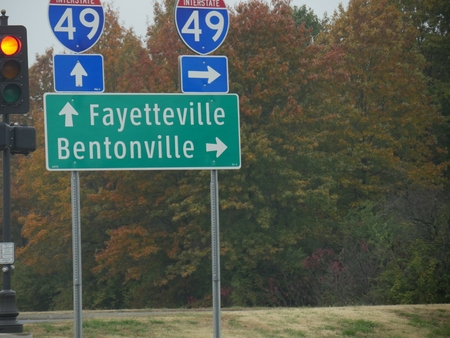 Close up of roadside signs and directions to Fayetteville and Bentonville, Arkansas along Interstate 49.