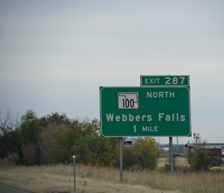 Roadside sign along the highway with directions and distance to Webbers Falls in Oklahoma. Sajtókép