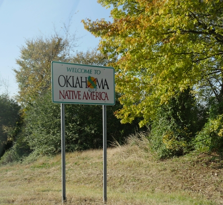 Roadside welcome sign to Oklahoma at the border past Arkansas near Moffett. Editorial
