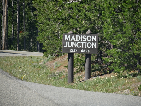 Roadside directional sign to Madison Junction with elevation information at Yellowstone National Park, Wyoming.