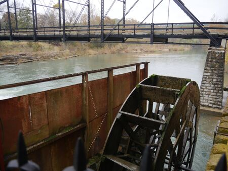 Top view of an old working waterwheel and a historic bridge in Arkansas.