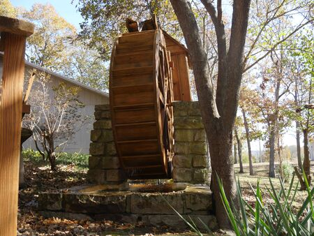 Wide side view shot of a functional new wooden waterwheel at a park