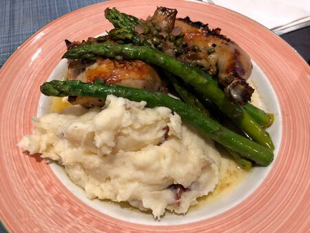 Close up of a plate of mashed potatoes, asparagus and baked chicken Stock Photo