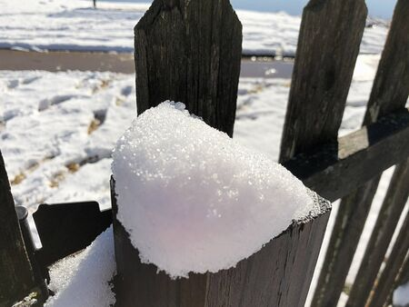 Close up of freshly fallen snow on top of a wooden fence post