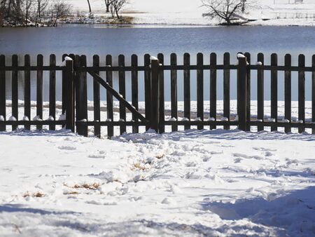 Fresh snow covers the ground, with a wooden fence and a pond in the background