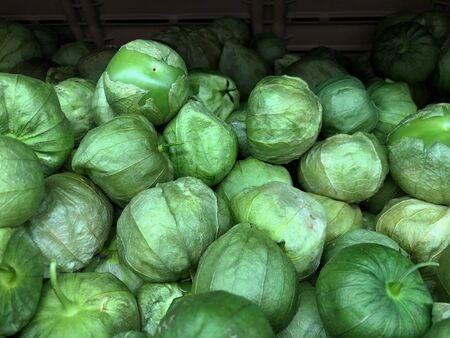 Wide shot of piles of tomatillos at a fresh produce section