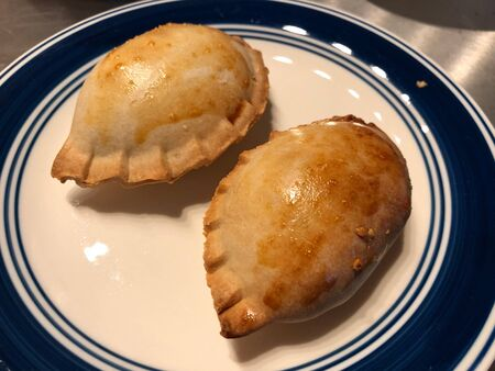 Two thick empanada rolls, a pastry snack with meat and vegetable stuffing