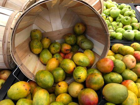 Medium close up of bushels of ripe mangoes at a fruit stall.