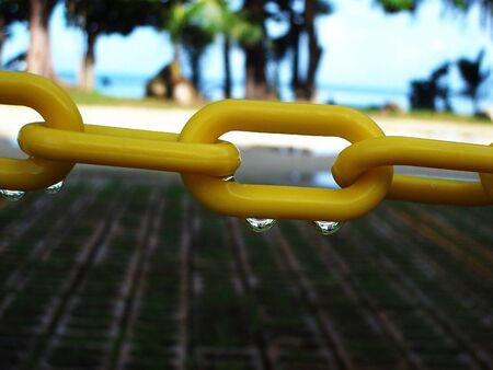 Two drops of water suspended from a link in a yellow chain