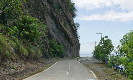 Governor Generoso, Davao Oriental, Philippines-March 2016: Winding paved road bordered by cliffs and the ocean at Governor Generoso, Davao Oriental. Foto de archivo