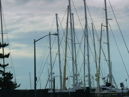 Newport, Rhode Island-September 2017: Poles for sailboats rising up to the skies from a dock at Goat Island, Newport. 스톡 콘텐츠