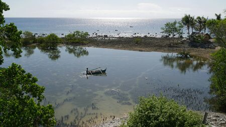 Small water inlet from seawater with a silhouette of a boat and a boy in the  southern Philippines. 스톡 콘텐츠