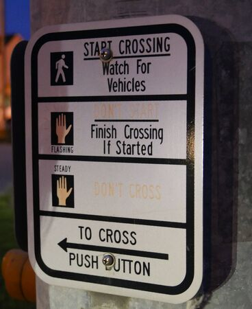 Close up of a sign at the pedestrian crosswalk in a highway.