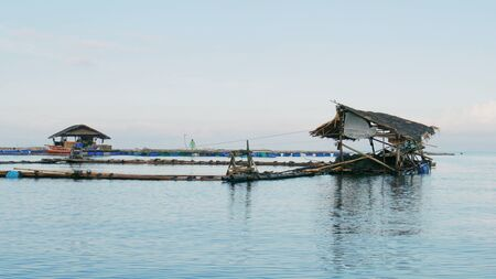 Banay Banay, Davao Oriental, Philippines - March 2016: Floating fish pens with thatched open cottages in Punta Linao, southern part of the Philippines. 스톡 콘텐츠
